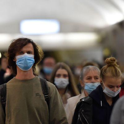 Personer i munskydd.