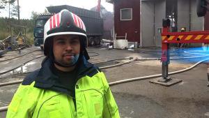 Brandman Terence Sam står framför en industrihall där eftersläckningsarbete pågår.