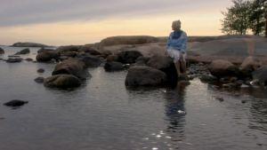 Irmelin Sandman Lilius sitter på en sten i havet.