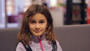 Barn med bruna ögon och brunt hår tittar in i kameran.