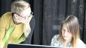 Anna Andersone tittar på hur en ung kvinna jobbar vid sin dator.