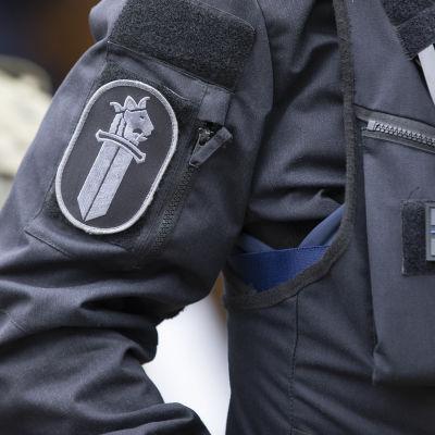 Svartkädd polis med armmärke.