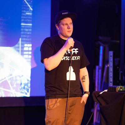 Benjamin står på en scen med en mikrofon i handen. Han ser lite nervös ut.