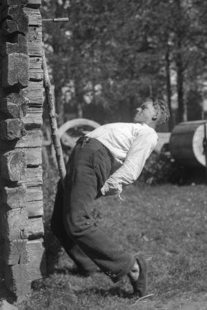En man försöker picka ned en kniv som är fast i en husvägg med en käpp som han har mellan sina ben. Bilden är tagen 1932 i Terjärv.
