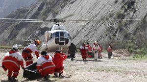 Röda korset i Iran bär bort kroppar från kraschat plan 12.3.2018.