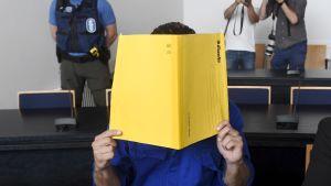 En person sitter och håller en gul mapp framför ansiktet i en rättegångssal. En polis och två fotografer står i bakgrunden av bilden.