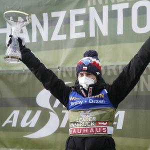 Kamil Stoch står med en pokal i handen och jublar.