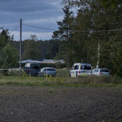 Ett trähus och parkerade bildar syns från en åker. Bland bilarna finns också en polisbil.