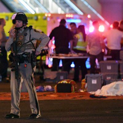 En polis talar i en walkietalkia i närheten av det område där dödsskjutningen i Las Vegas inträffade.