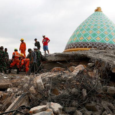 Avustustyöntekijöitä romahtaneen moskeijan raunioilla Lombokilla.