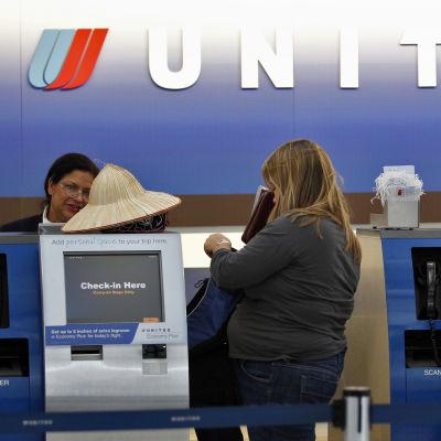 Människor vid en incheckningsdesk på en flygplats. På väggen står det United.