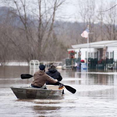 Asukkaat melovat tulvavesissä St. Louisin lähellä Missourissa.  Vesi peitti alleen asuntovaunualueen.