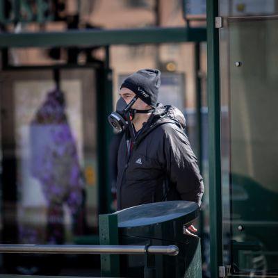 Hengityssuojainta käyttävä mies kadulla