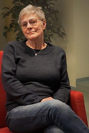 Medelålders kvinna poserar i en röd soffa.