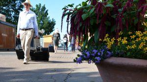 En man i sommarkläder drar en kappsäck bakom sig längs med aura Å. Blommor i en kruka i förgrunden.