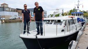 Calle Storm och Niklas Löfberg står på fören av en vit passagerarbåt.