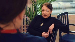 Katariina Forssell sitter på en stol och talar med en vårdare ur Almahemmets personal.