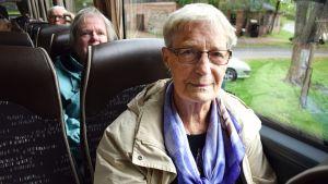 Lisbeth Nyberg, som har på sig en beige jacka och lila scarf sitter i en buss.