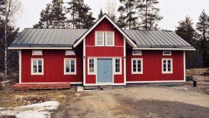Ett rött, nybyggt sekelskiftes hus med plåttak och blåa dörrar.