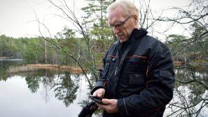 Bo vilander framför en sjö, tittar ner i sin mobiltelefon.