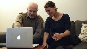 Sanna-Mari och Panu Kunttu sitter i en soffa och tittar på Europas karta på en dator.