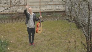Janne Grönroos vinkar med en gitarr i handen