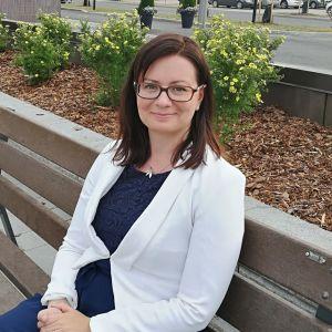 Ylivieskan kaupunginjohtaja Maria Sorvisto istuu puistonpenkillä.