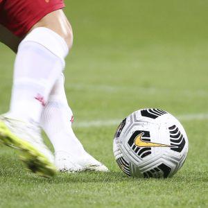 Tunnistamaton henkilö potkaisemassa jalkapalloa.