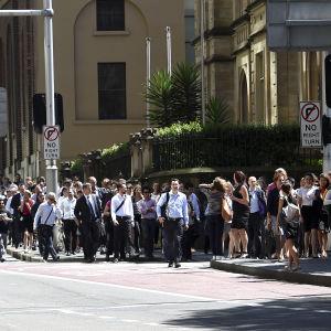 Kontorsanställda evakueras från sina arbetsplatser i affärsdistriktet i Sydney där ett gisslandrama pågår i ett kafé.