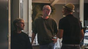Man med glasögon står i mörklagt kafé och pratar med en man med hatt.