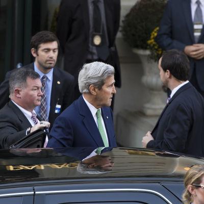 USA:s utrikesminister vid sin bil omringad av säkerhetsmän.