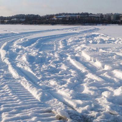 Jyväsjärven jäällä moottikelkan jälkiä lumessa.