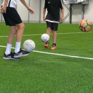 tre pojkar står och trixar med fotboll