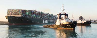 Fartyget Ever Given i Suezkanalen. Två räddningsbåtar syns bredvid fartyget.