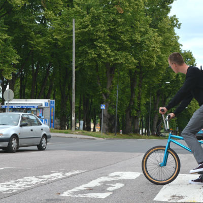 Cyklist på väg ut på övergångsställe, bil kommer emot.