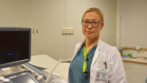 Kvinnlig läkare i sjukhusrum tittar in i kameran.