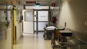 En korridor på Borgå sjukhus. Invid den högra väggen står en sjukhussäng och en rullstol. Till vänster är en öppen dörr.