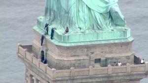 Kvinna sitter på foten till Frihetsgudinnan medan poliser försöker klättra upp till henne.