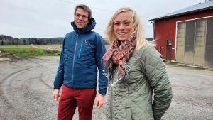 Ida Fredriksson och Tomas Björkroth framför en åker i höstigt, blåsigt väder.