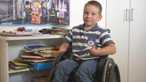 Liten pojke sitter i rullstol