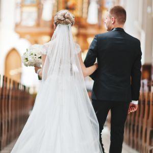 Brudpar går uppför altaret i en ståtlig kyrka.