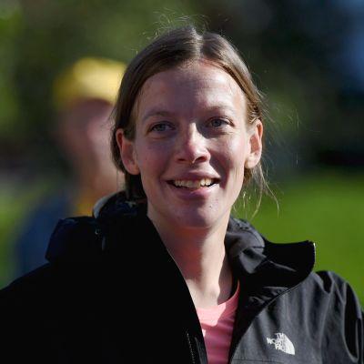 Li Andersson klädd i svart sportrock med händerna i sidorna och ett leende på läpparna.