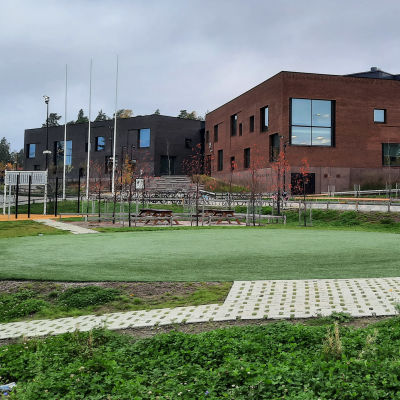 En stor brun tegelbyggnad vid en skolgård.