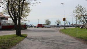 En väg vid havet, bilar står parkerade, till vänster en byggnad, gräsmatta, sol, sommar.