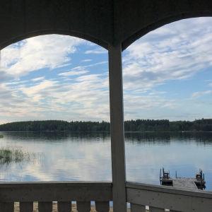 Rauhallinen ja kesäinen järvimaisema rannalta huvimajasta katsottuna.