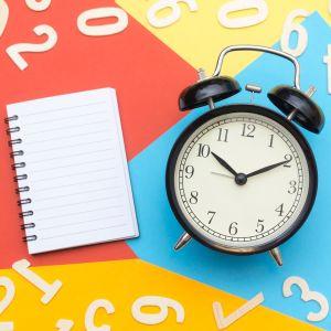 Vanhanaikainen herätyskello, muistilehtiö ja numeroita värikkäällä alustalla.