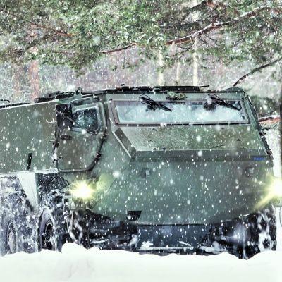 Panssaroitu ajoneuvo talvisessa metsässä.