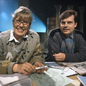 Täysi kuu -ohjelman juontajat Ulla Roihu ja Ari Meriläinen pöydän ääressä.