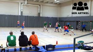 Två handbollslag spelar i en match.
