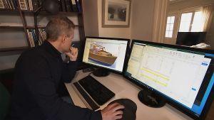 En man sitter vid en dator och på skärmen finns en 3d ritning av en båt.